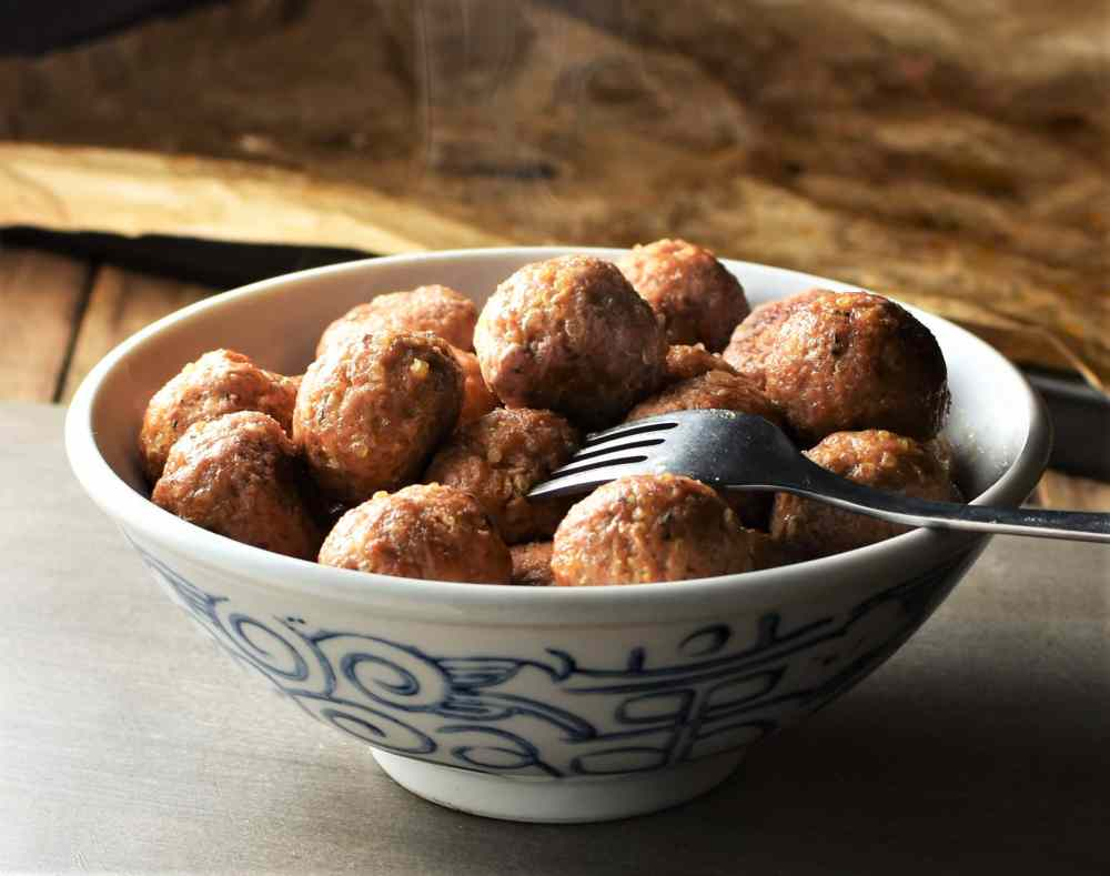 Side view of meatballs in white bowl with fork.