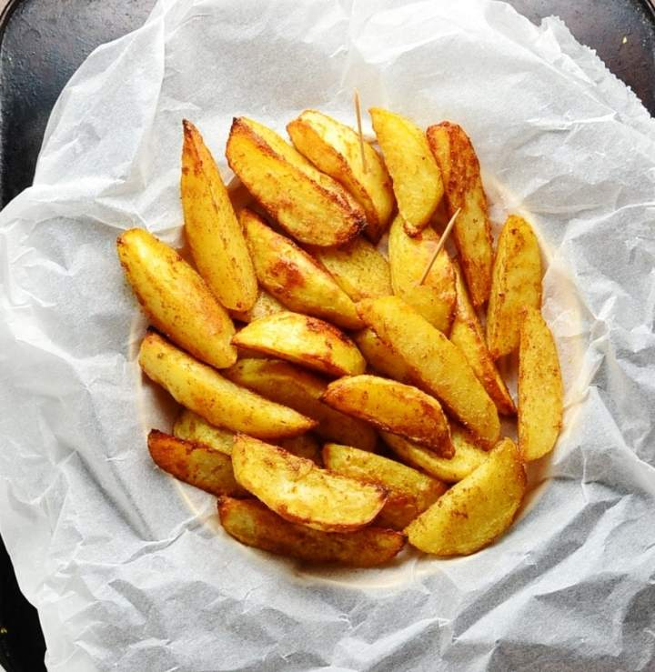 Spiced potato wedges on top of parchment paper.