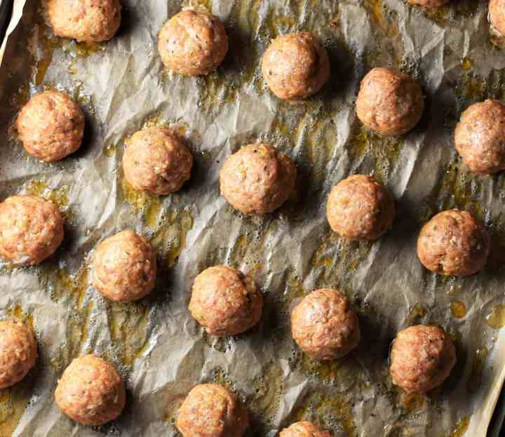 Baked meatballs on top of parchment.