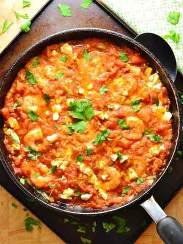 Tomato shrimp saganaki in large black pan on oven tray with spoon and green cloth.