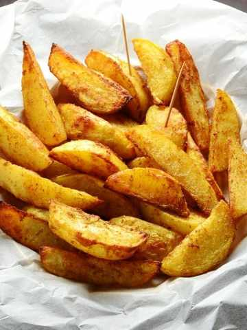 Spiced crispy potato wedges with cocktail sticks in basket lined with white paper.