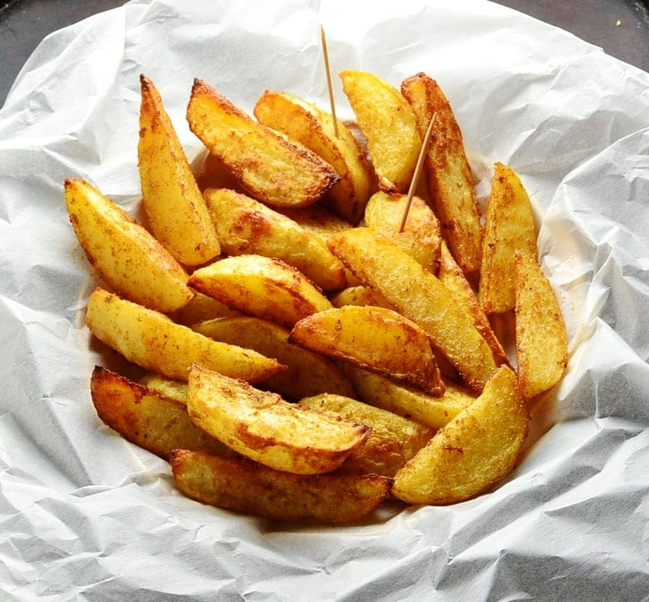 Spiced crispy potato wedges with toothpicks in basket lined with white paper.
