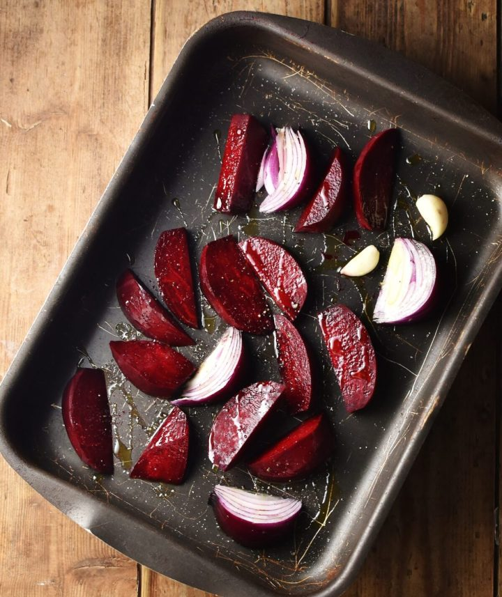 Beet wedges and red onion wedges with 2 garlic cloves in tray.