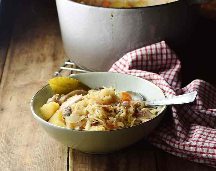 Side view of sauerkraut, chicken and potato casserole in green bowl with spoon, red-and-white cloth and large white pot in background.