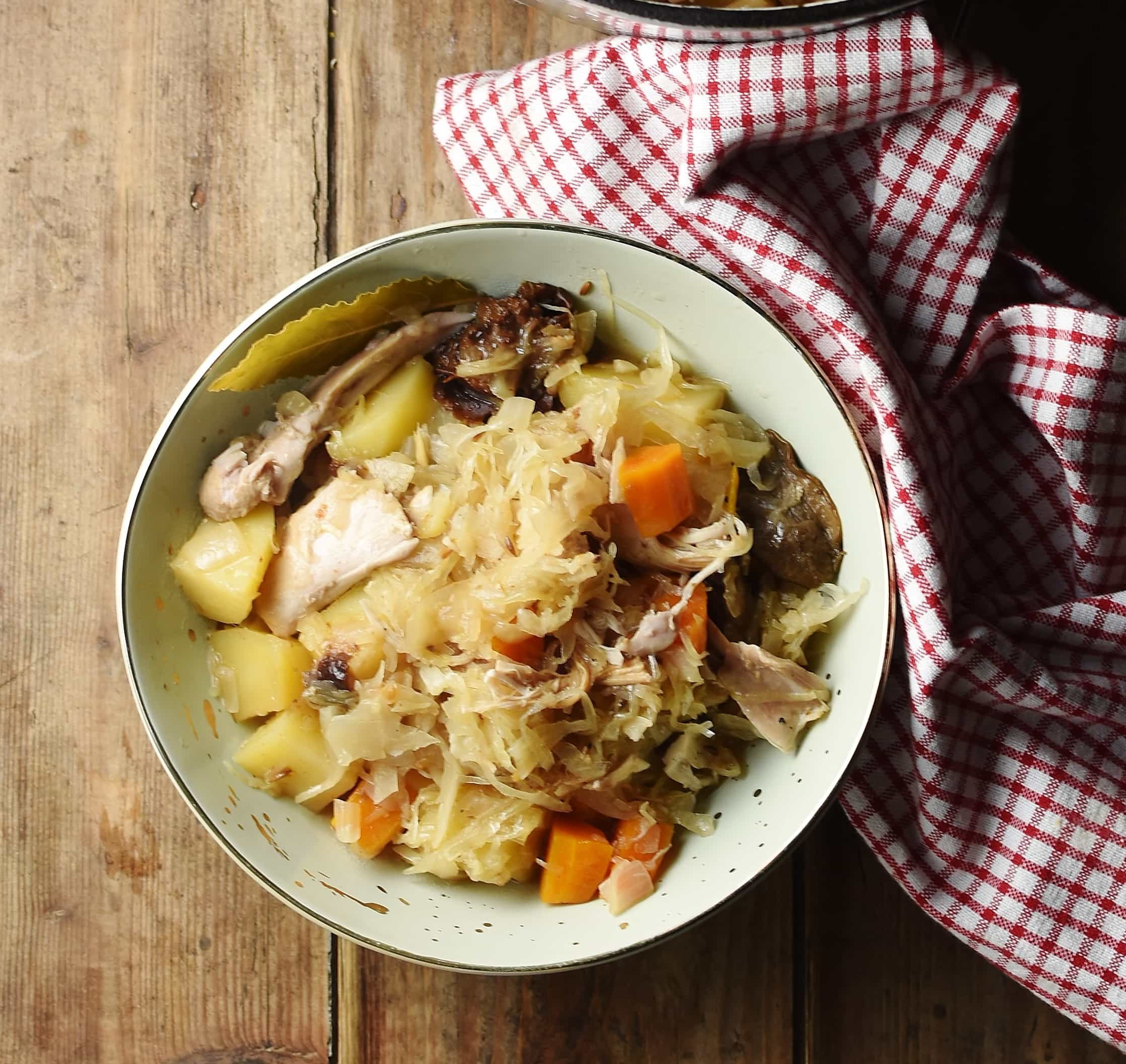 Sauerkraut, chicken, potato, carrot stew in green bowl with red-and-white checkered cloth to the right.