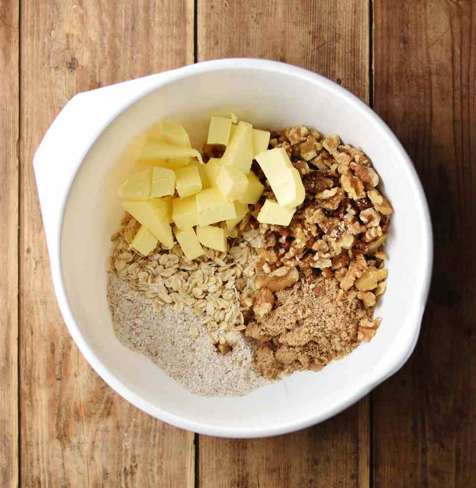 Cubed butter, oats, flour, walnuts and brown sugar inside large white bowl.