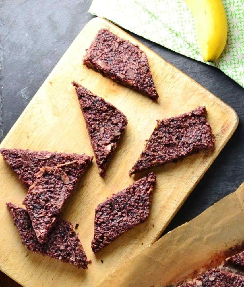 Top down view of blackberry oat bars on top of large wooden board, with banana on top of green cloth in top right corner.