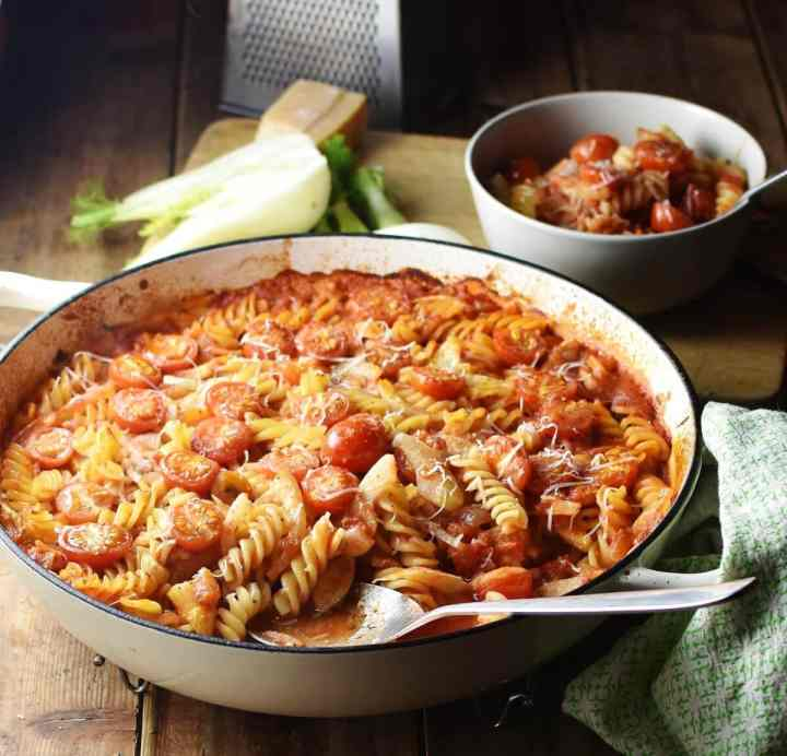 Fussili pasta with sliced fennel and tomato sauce in large white casserole dish with spoon, pasta and sauce in bowl, halved fennel and grater in background.