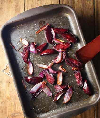 Roasted beetroot and red onion wedges in tray with red spatula.