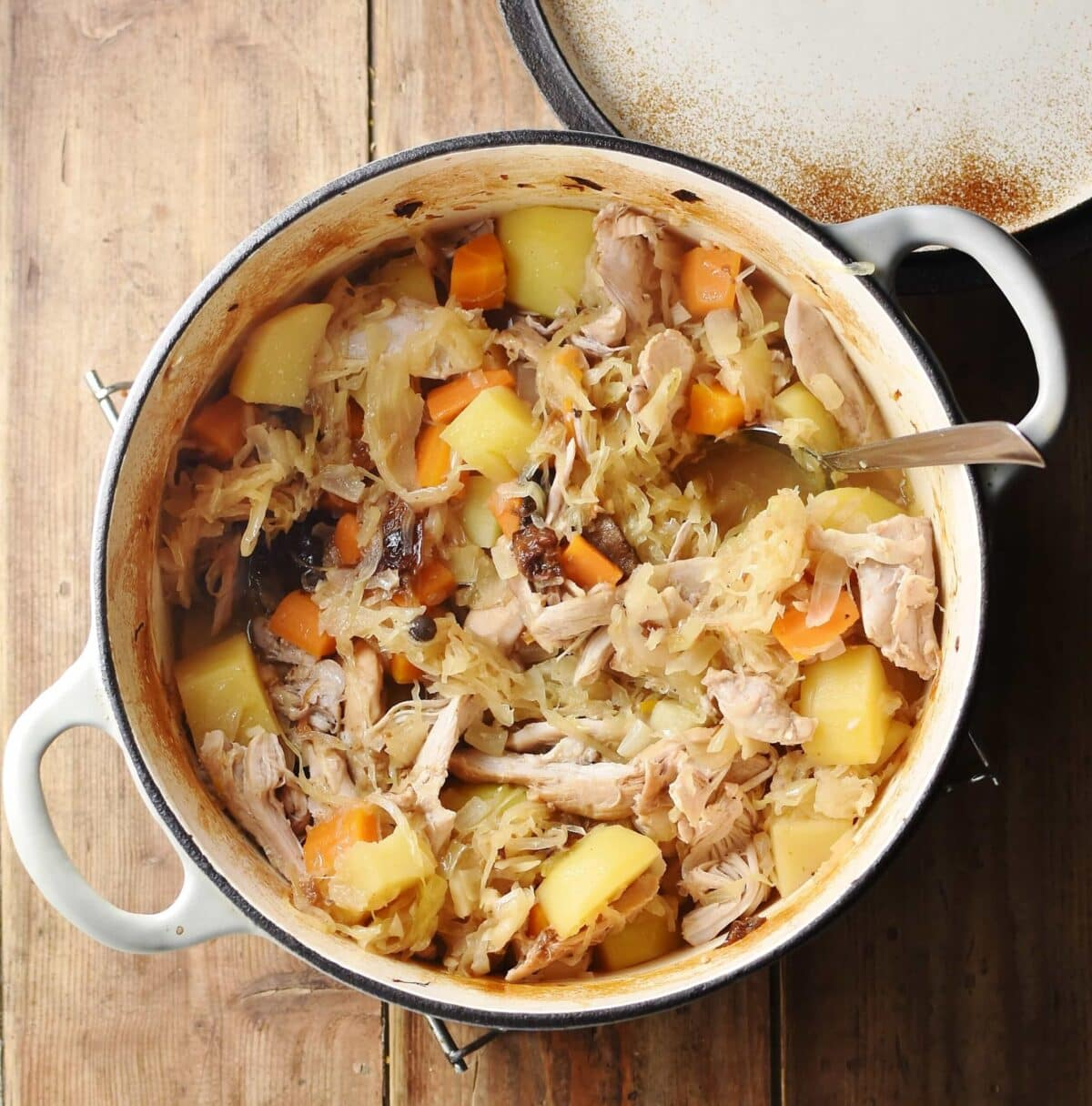 Potatoes, carrots, chicken pieces and sauerkraut in large white pot with spoon and lid in top right.