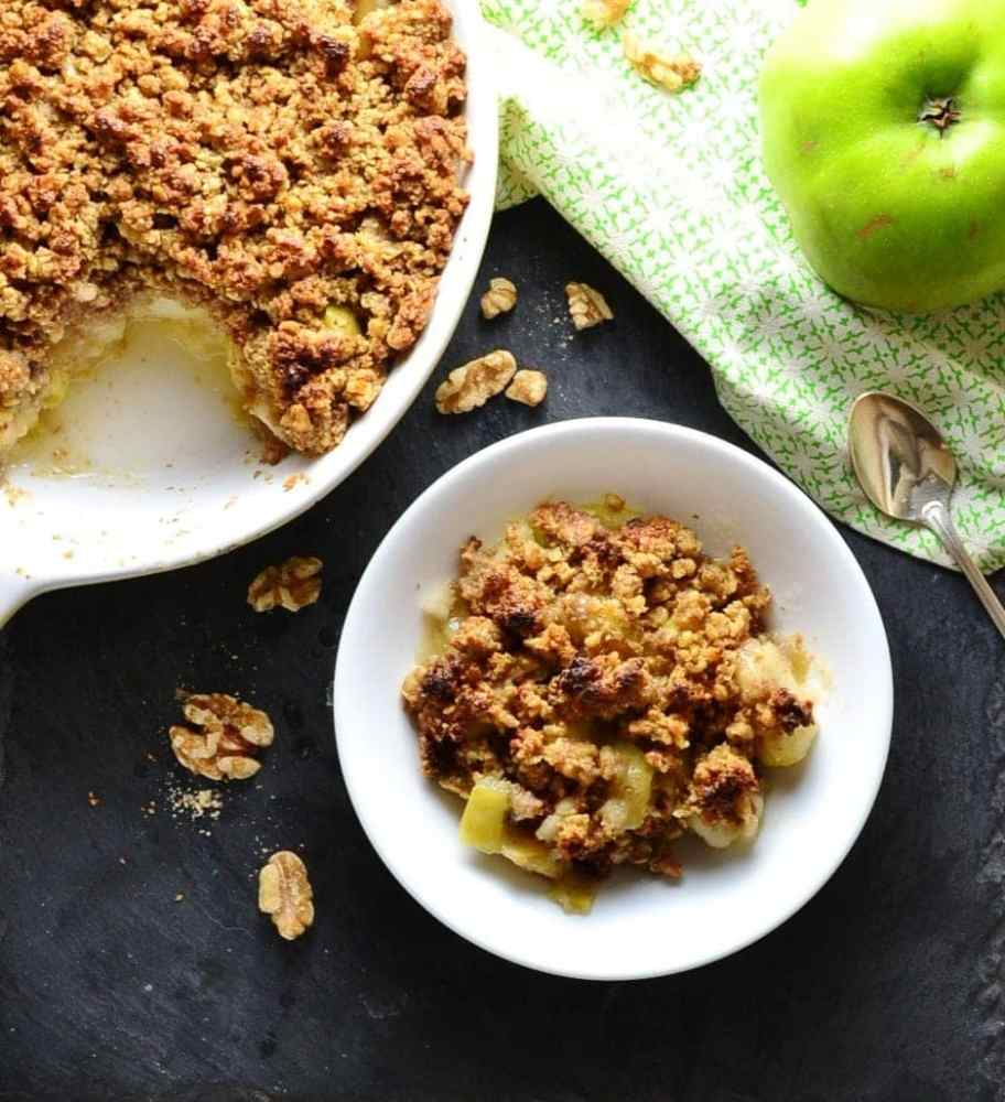 Apple crumble in white dish and white bowl with green cloth and green apple with spoon on top and walnuts scattered around.