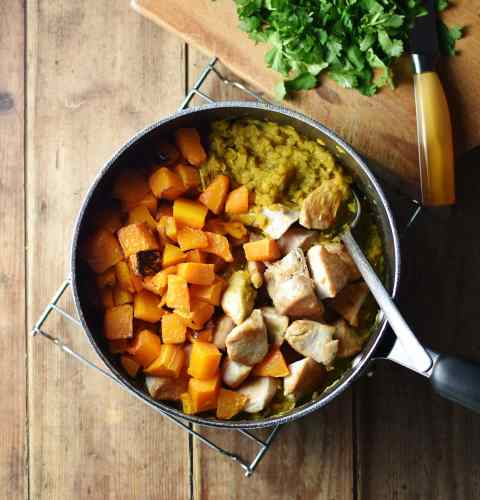 Chicken pieces, cubed, roasted squash and lentil sauce inside large pot with spoon, with chopped herbs on top of cutting board in top right.
