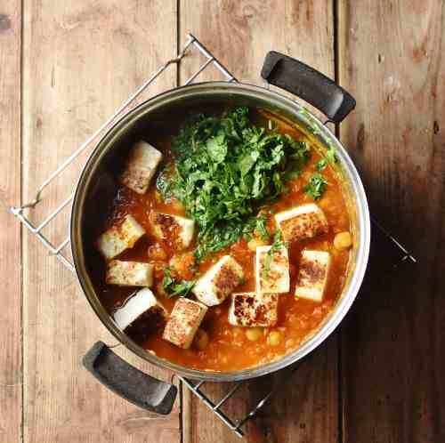 Tomato sauce with fried pieces of paneer cheese and chopped herbs in pot.