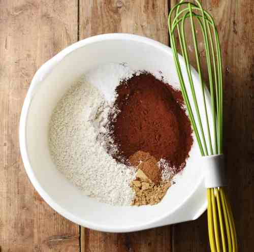 Flour, cocoa and spices in large white bowl with green whisk.