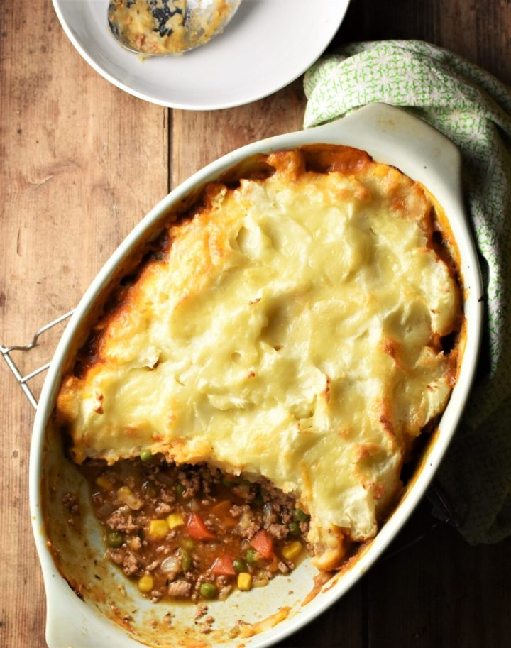 Top down view of turkey shepherds pie in green oval dish, with green cloth and white plate in background.
