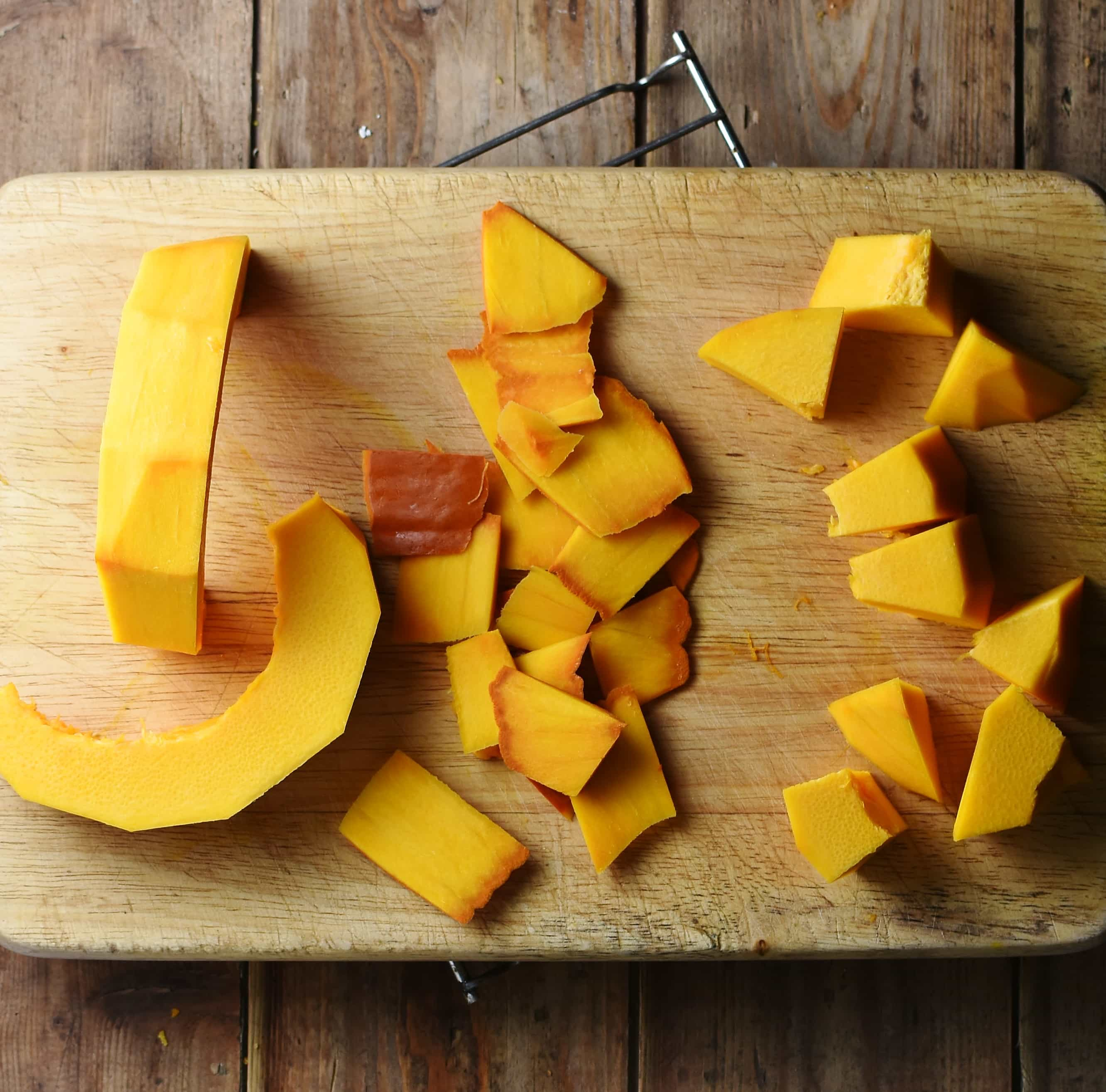 Peeled and chopped pumpkin on wooden board.