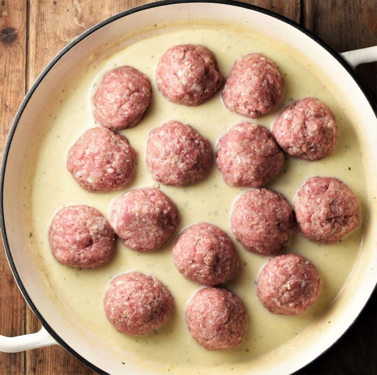 Raw meatballs in white sauce in large shallow pan.