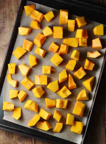 Cubed pumpkin on top of baking sheet lined with paper.