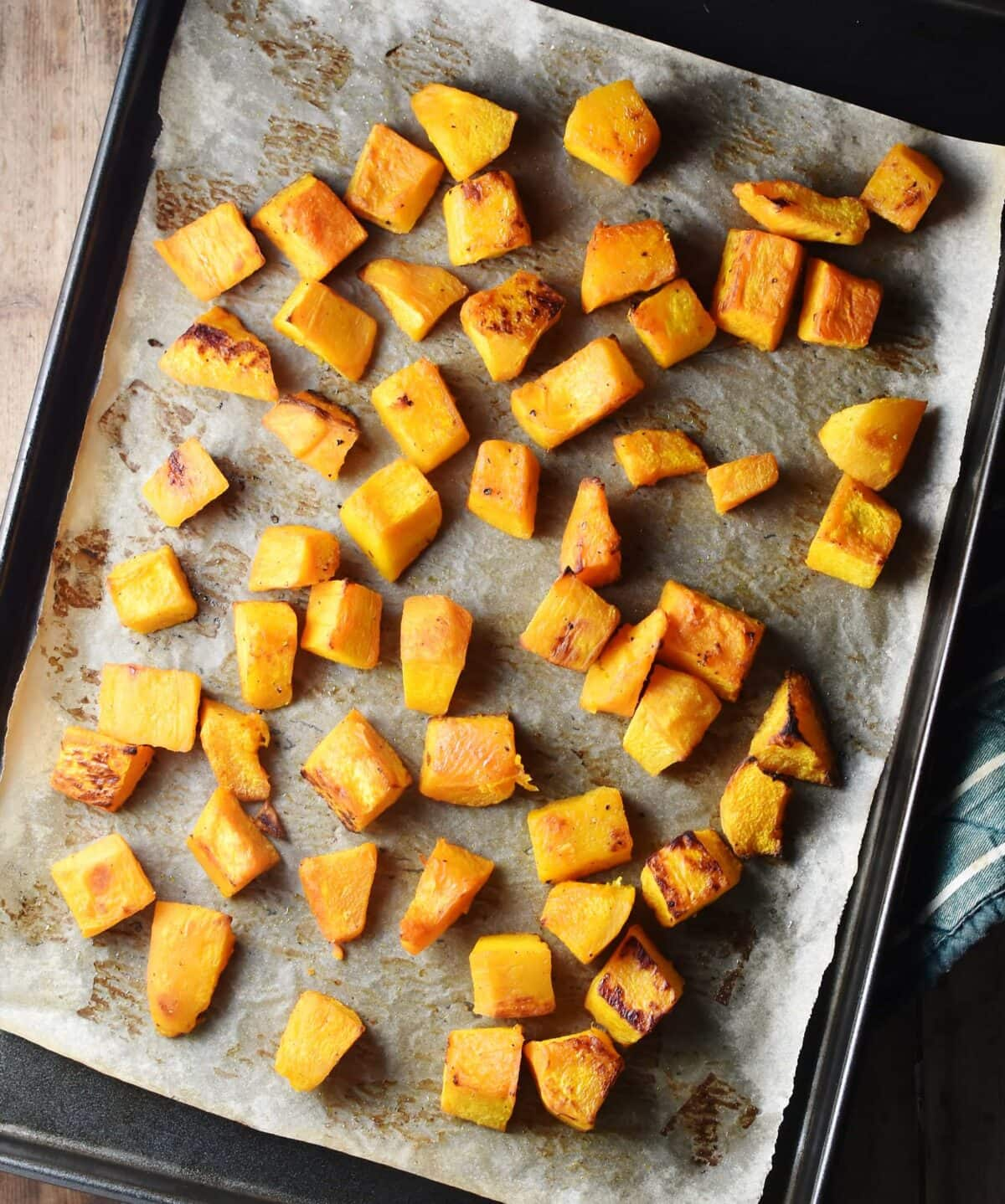 Roasted pumpkin cubes on top of baking sheet lined with parchment paper.