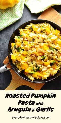Pumpkin with pasta and herbs in skillet on top of cutting board.