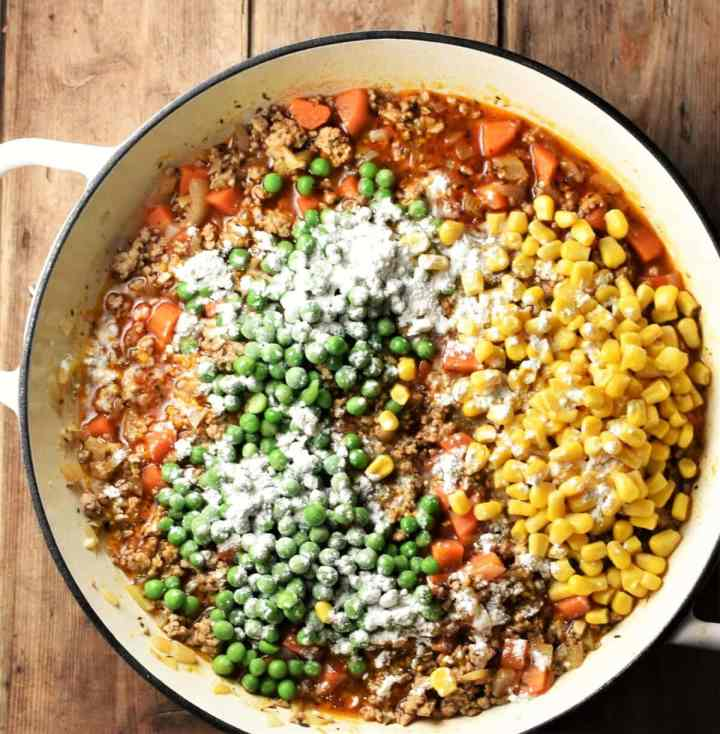 Turkey mince in sauce with corn, carrots, peas and flour over the top on large white shallow dish.