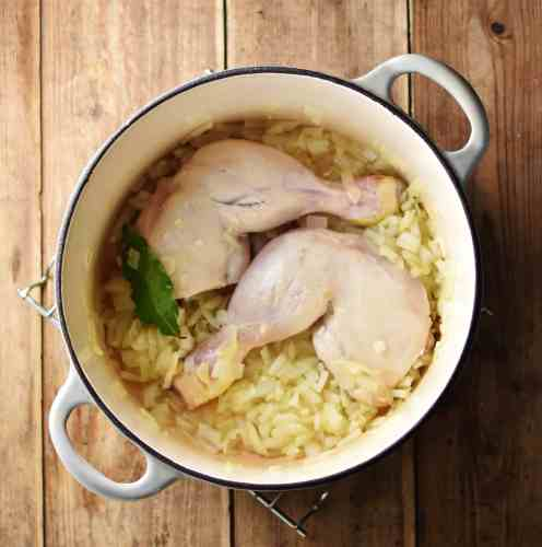 2 chicken leg quarters with bay leaf and onions in white pot.