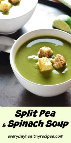Pea soup with croutons in white bowl with lime in background.