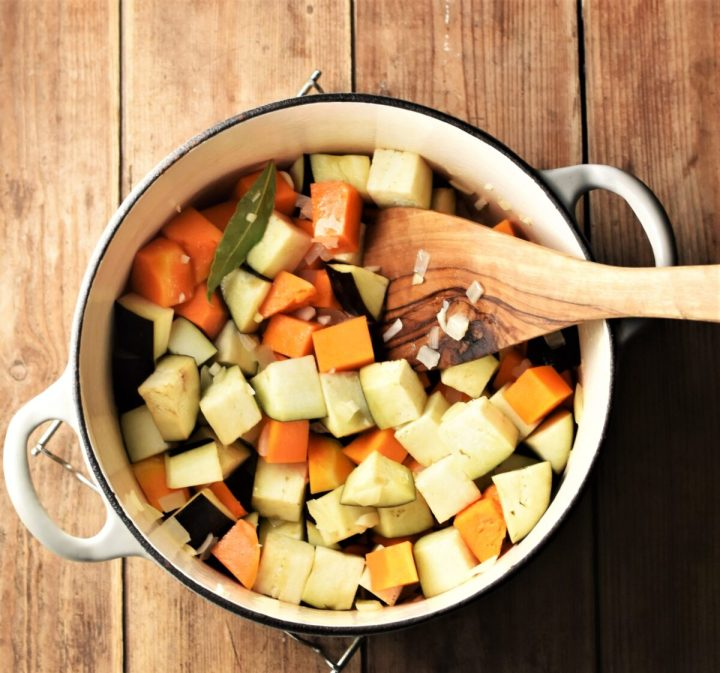 Cubed squash and eggplant in large white pot with wooden spoon.