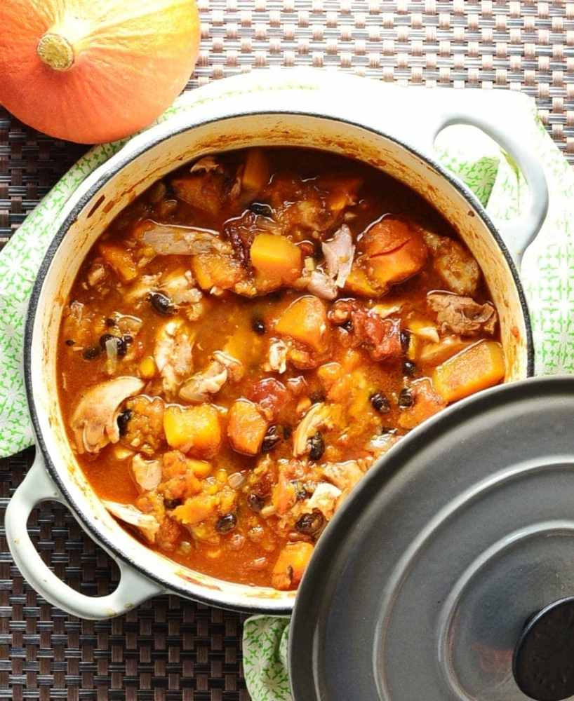 Chicken butternut squash casserole in white pot with grey lid on green cloth with squash.