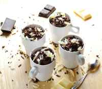 Cheesecake pots with white and dark chocolate shavings, chocolate pieces and spoon on wooden surface.