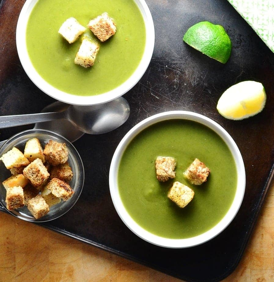 Top down view of green pea soup in 2 white bowls with croutons, lime wedges, spoons and dish of croutons on oven tray.