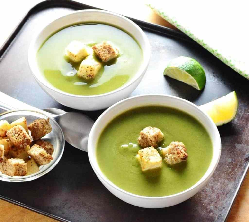 Green pea soup in 2 bowls with croutons, lime wedges, croutons in small dish and spoons on dark oven tray.