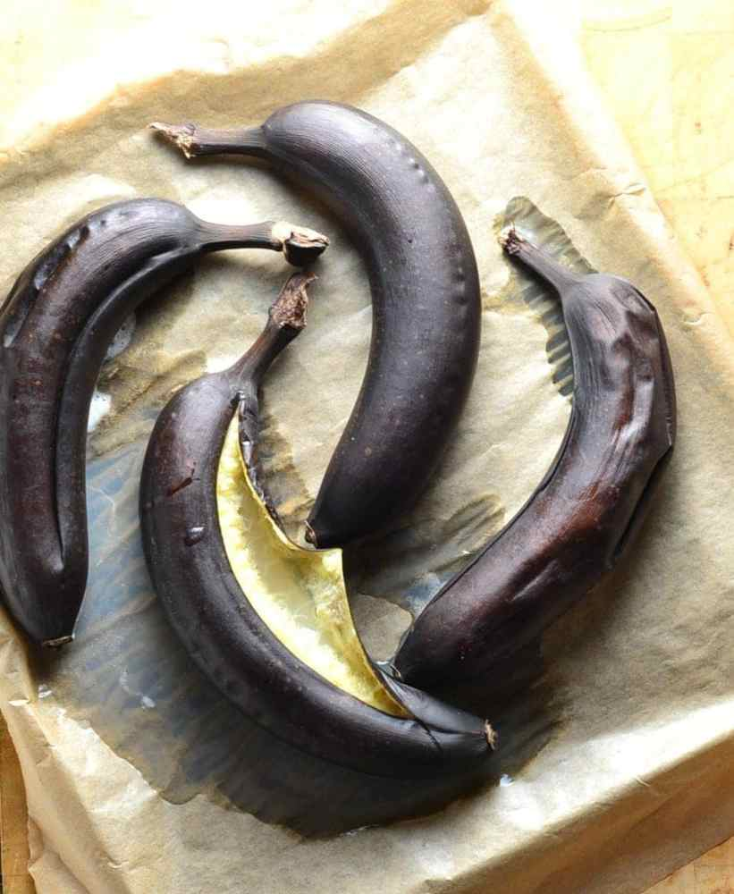 Top down view of 4 dark brown baked bananas on tray lined with baking paper.