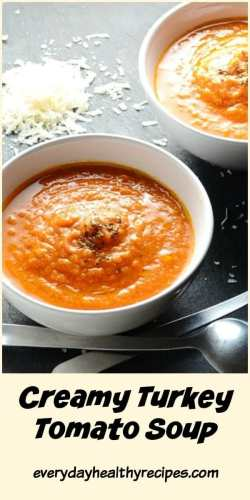 Side view of creamy tomato soup in white bowl, with 2 spoons in front.