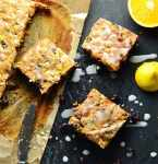 Top down view of fruit cake slices on top of grey surface with halved lemon and orange, as well as knife.