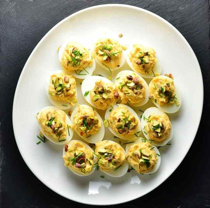 Top down view of smoked salmon deviled eggs with garnish of pistachios and chives on white plate.