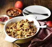 Vegetarian stuffing in white oval dish with spoon and red-and-white cloth to the right,plates and forks, chestnuts and apple in background.