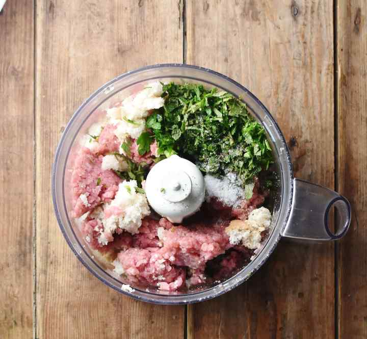 Ground turkey, chopped herbs and pieces of bread inside blender.