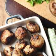 Stuffing meatballs in rectangular dish.