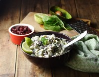 Side view of creamy turkey salad with lime wedges and spoon in purple bowl, with dried cranberries in red dish, mint leaves, lime, avocado peel and green cloth in background.