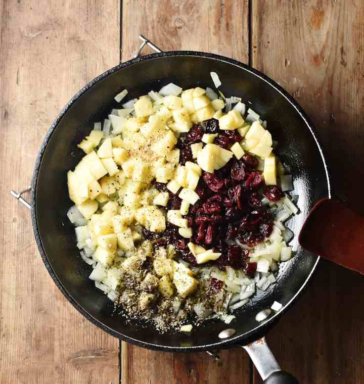 Chopped apple, cranberries, onions and spices in skillet with red spatula ti the right.