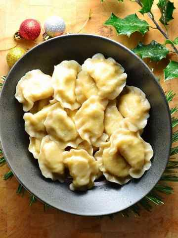 Top down view of Polish pierogi in black bowl on top of wooden table with Christmas decorations.