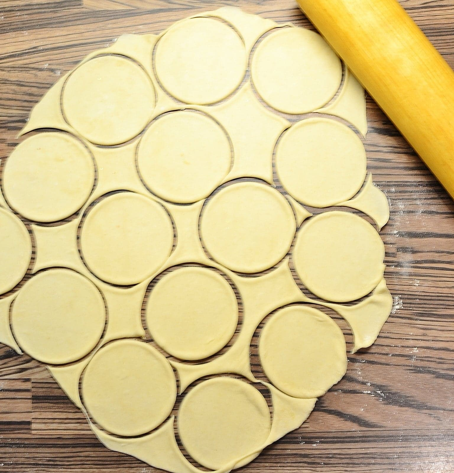 Rolled out dough with cut out circles and rolling pin in top right.