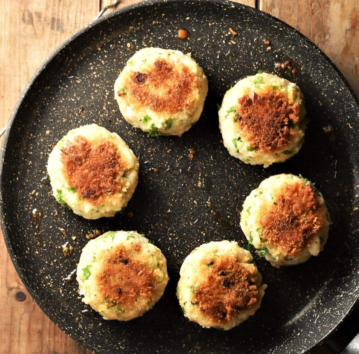 Top down view of 6 fried fishcakes in pan.