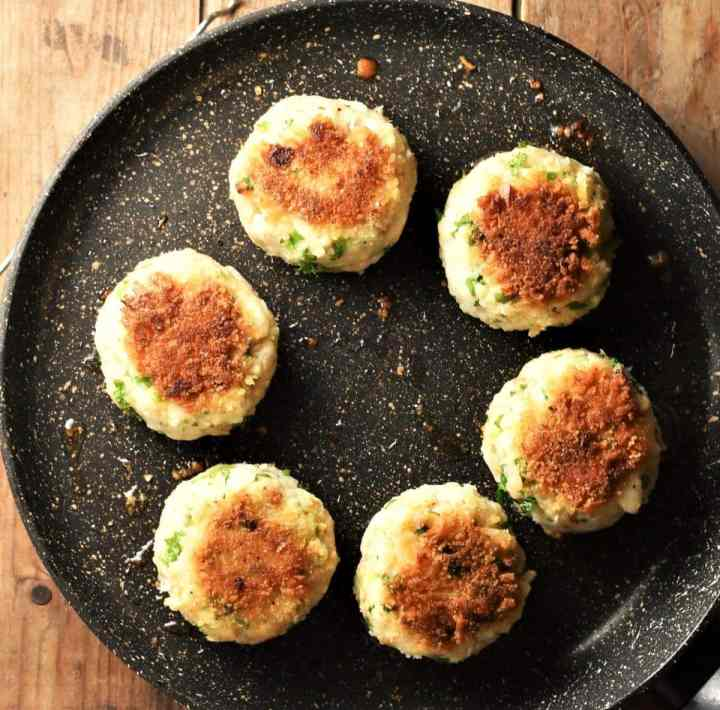 Top down view of 6 fried fishcakes in pan.