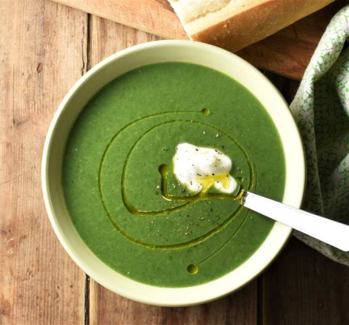 Cream of spinach soup in green bowl with spoon, baguette and green cloth in background.