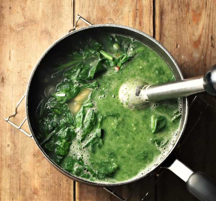 Partly pureed spinach soup in large pot with stick blender end piece.
