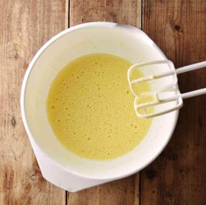 Beaten egg mixture inside white bowl.