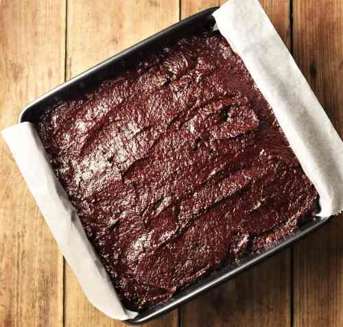 Beet brownie batter in square pan lined with parchment paper.