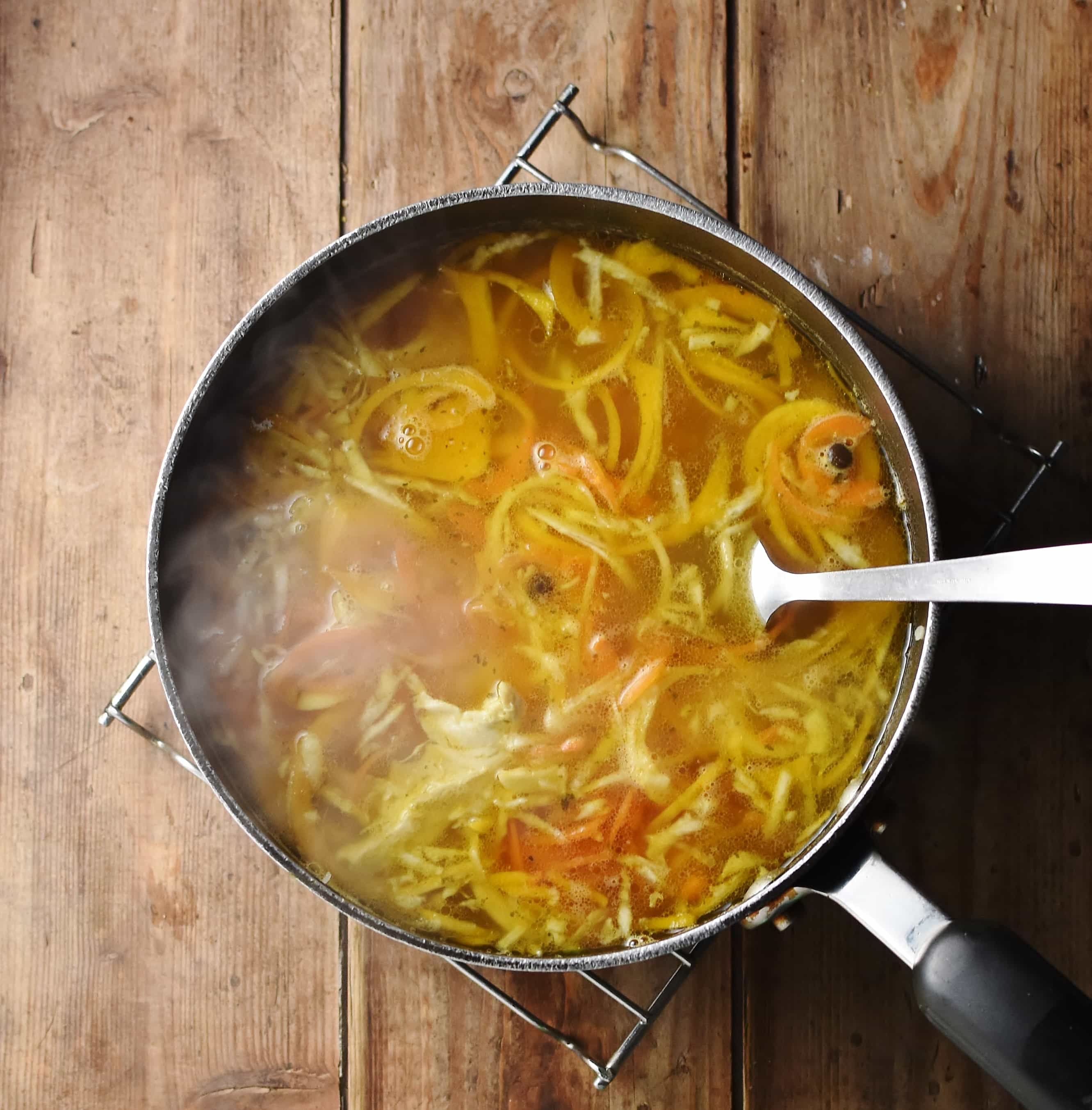Spiralized vegetable chicken soup with steam in large pot with spoon.